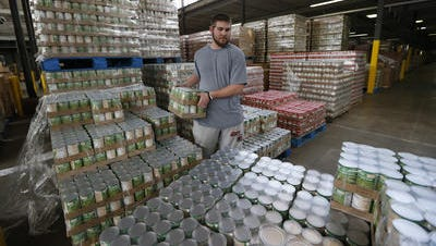 Dalton Taylor stacks green beans at the Freestore Foodbank.