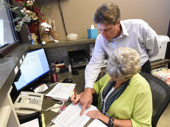 Baxter County Sheriff John Montgomery goes over a report with Gayla Tate on Thursday at the sheriff's office.