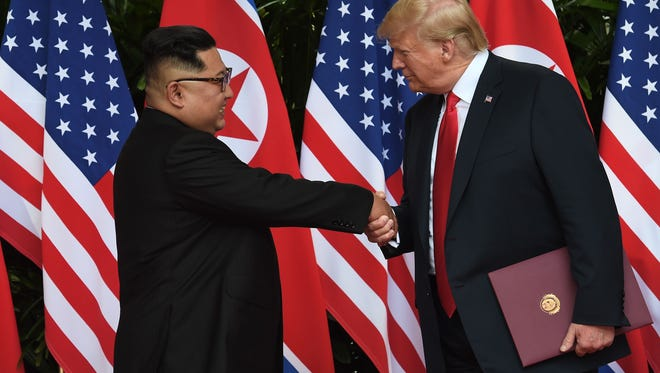 North Korea's leader Kim Jong Un shakes hands with President Trump after taking part in a signing ceremony at the end of their historic US-North Korea summit, at the Capella Hotel on Sentosa island in Singapore on June 12, 2018. Trump and North Korean leader Kim Jong Un hailed their historic summit on June 12 as a breakthrough in relations between Cold War foes, but the agreement they produced was short on details about the key issue of Pyongyang's nuclear weapons.