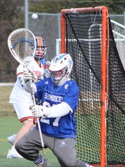 Catholic Central goalie Jakob Hemme (27) goes for the
