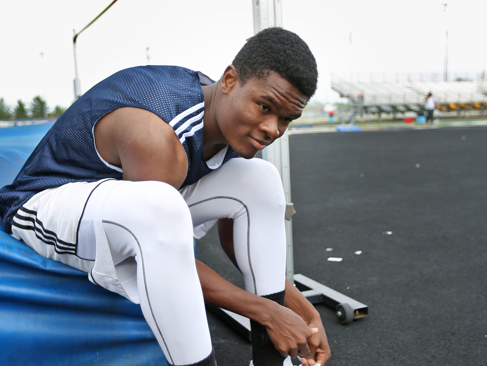 HSE's Francis Ehigbai puts on his shoes for high jump practice, June 1, 2015.