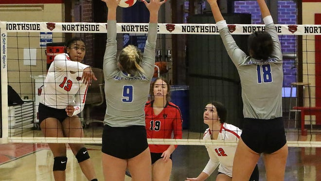Northside's Hannah Smith (center) and Macie Grams (right) play defense as Za'Kari Gurule' hits over Bryant's Ella Reynolds, left, and Samantha Ferguson in the first set, Tuesday, Oct. 20, at Kaundart-Grizzly Field House.