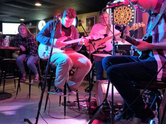 Ryan Newton (left) and Alec Young (right) sit in with Alec's dad Bob Young at Flynn's Roadhouse Café's Wednesday night jam session.