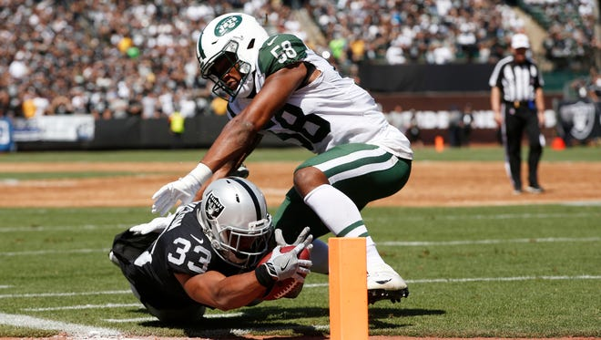 Jets outside linebacker Darron Lee (58) tackling  Oakland Raiders running back DeAndre Washington  in the first quarter at Oakland Coliseum when the Jets played the Raiders on Sept. 17, 2017.