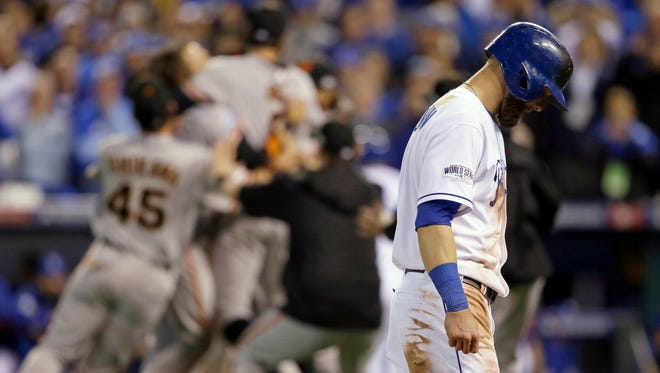 Kansas City Royals' Alex Gordon (4) walks off the field as San Francisco Giants players celebrates after Game 7 of baseball's World Series Wednesday, Oct. 29, 2014, in Kansas City, Mo.