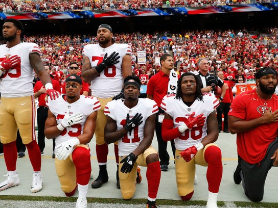 Member of the San Francisco 49ers kneel and stand during the playing of the National Anthem before an NFL football game against the Washington Redskins in Landover, Md., Sunday, Oct. 15, 2017. Kneeling are (L-R) strong safety Eric Reid (35), wide receiver Marquise Goodwin (11) and defensive back Adrian Colbert (38). (AP Photo/Alex Brandon)