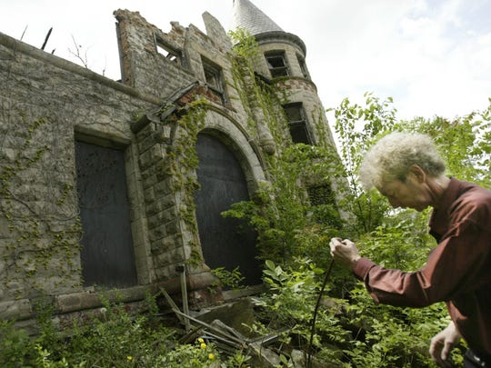 Developer Joel Landy shows the exterior of the James Scott mansion at the corner of Peterboro and Park in Detroit in May 2004.
