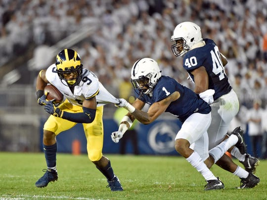 Michigan's Donovan Peoples-Jones carries the ball against Penn State's Christian Campbell (1) and Jason Cabinda (40) in the second half of an NCAA Division I college football game Saturday, Oct. 21, 2017, at Beaver Stadium. The No. 2 Penn State Nittany Lions defeated Michigan 42-13, improving their season record to 7-0.