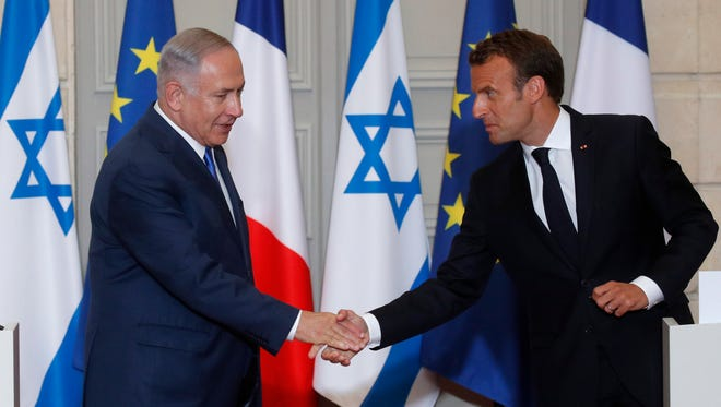 French President Emmanuel Macron and Israeli Prime Minister Benjamin Netanyahu meet for a joint news conference Tuesday in Paris.