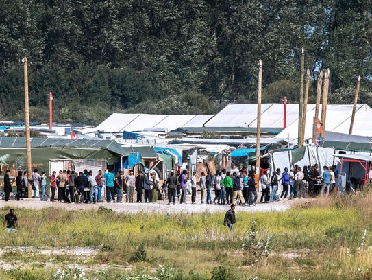 Migrants stand in line in 'The Jungle' migrant camp,