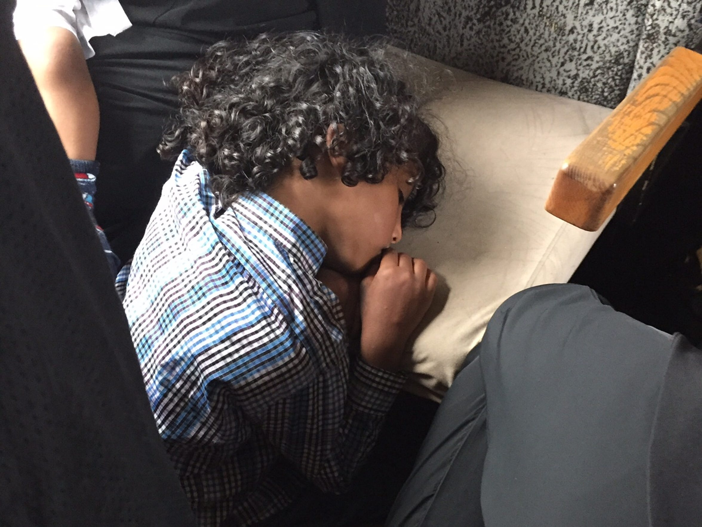 A boy rests his head on a seat on a train traveling