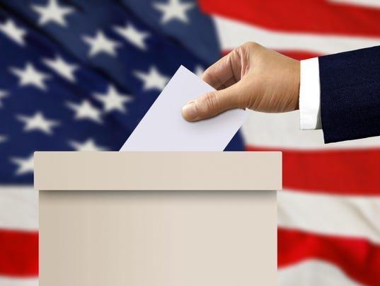 Ballot box with person hand casting a vote