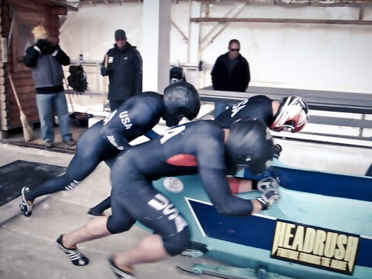 Codie Bascue (driver), Kazden Ikehara (closest), Nathan Crumpton (brakeman) and Colin Coughlin (far side) are shown competing in Bascue's four-man sled in a 2013 North America's Cup race at Lake Placid.