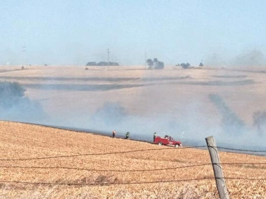 Fire fighters search for hot spots as smoke rises from a recently burned field during a grass/field fire that burned approximately 500 acres south of Ewart.