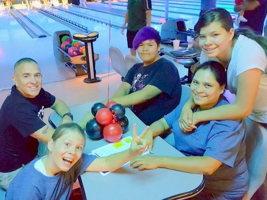 Big Brother Leonard Maldonado, left, sits across from his Little Brother, Dmitri Bitsilly, at last year's Big Brothers/Big Sisters Bowl for Kids' Sake fundraiser at Bowlero Lanes in Farmington. Also pictured at front are Shannon Teseney and her children Lillian and Raymond Davis, who participate in the school-based Big Brothers/Big Sisters program.