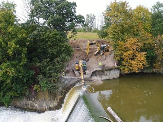 Work crews cut notches in the Ballville Dam on Wednesday as a step toward the dam's planned demolition in 2018.