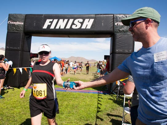 A runner crosses the finish line to receive a drink
