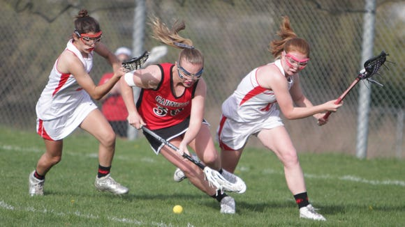 Rye's Margaret Mitchell (center) goes up for a loose ball against North Rockland's Amanda Squillini (left) and Caeli Porrette (right) during a Section 1 girls lacrosse game between North Rockland and Rye at North Rockland High School on Monday, April 18th, 2016. North Rockland won 10-5.