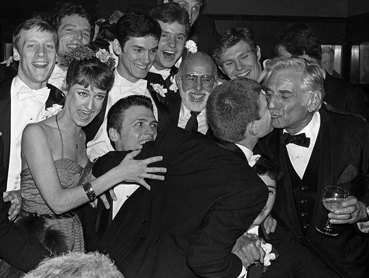 Leonard Bernstein, right, gets a kiss from one of the