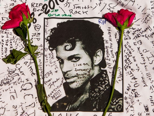 Flowers lay on a T-shirt signed by fans of singer Prince