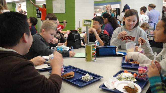 Students eat lunch in the cafeteria at D.C. Everest Middle School in this 2013 file photo. The price of school lunches is creeping up for students this year.