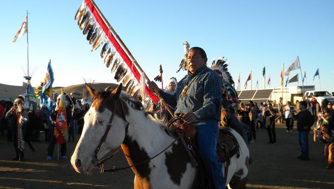 Tuffy First from the Fort Peck Indian Reservation carries in an eagle staff Wednesday into the camp on the Standing Rock Indian Reservation. The tribe is in support of the Standing Rock Sioux Tribe's opposition to the construction of the Dakota Access Pipeline near their lands.