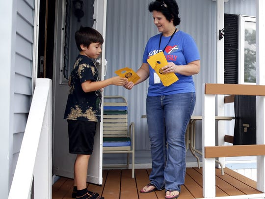 Lisa Madsen, fifth-grade teacher at Doty Elementary in Allouez, gives third-grade student Rafael Guerrero-Vazquez information about the start of the school year.