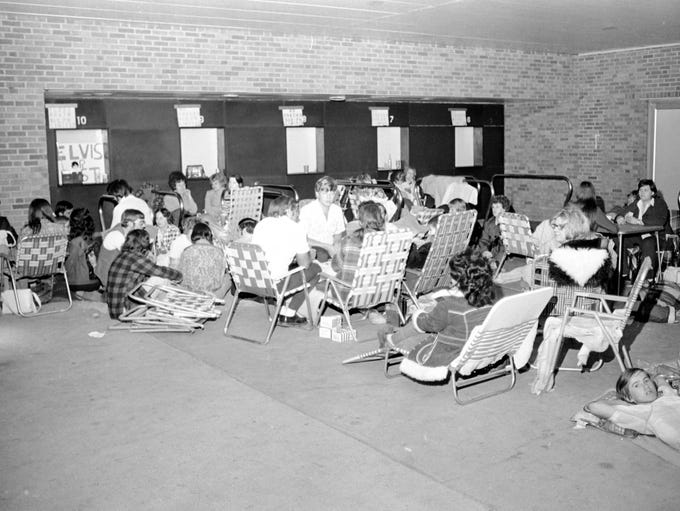 Fans waiting to buy tickets for Elvis Presley, sitting