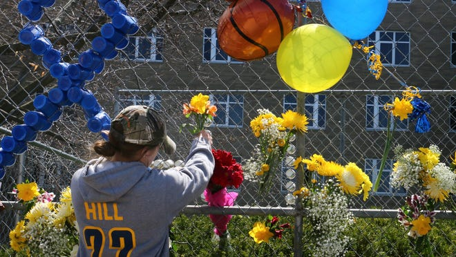 A member of the Mount St. Joseph womens basketball team places a flower in a memorial during a tribute to basketball player Lauren Hill at Mount St. Joseph College in Cincinnati Friday April 10, 2015. Hill died of brain cancer Friday. (AP Photo/Tom Uhlman)