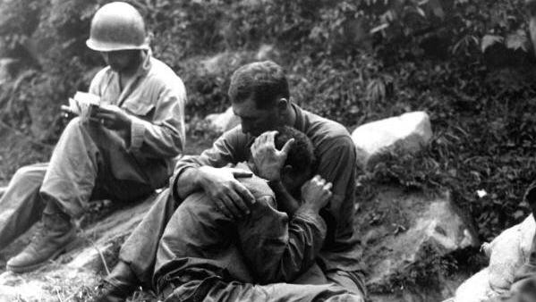 A Medic does the paper work while a Soldier weeps for a lost buddy. Korea - 1950-53