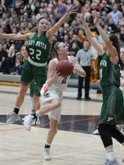 Grinnell Tiger Macy Harris aims for a basket as Pella's Kara Wichart, 22, and Emily Holterhaus, 34, try to block in the Class 4A Region 6 title game won by the Tigers 84-47.
