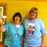 Sharon Hassett and Cheryl Partin show off the medals they won in the annual Senior Olympics.
