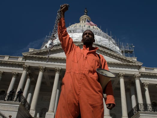 An activist dressed as a prisoner stands in front of