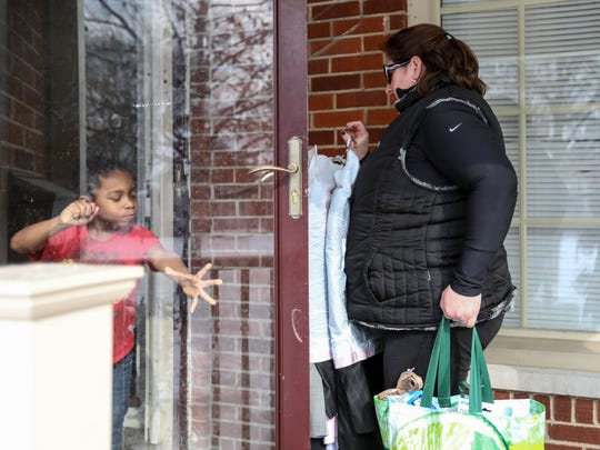Timothy Tarver, 5, of Detroit holds the door open for Erica Guido, 39, of Grosse Pointe Woods who stops by with donations for his family given to Guido through her grassroots organization, To Detroit With Love, on, Tuesday, Feb. 6, 2018.