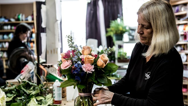 Nancy Gilmore-Ebner, who works at Griffen's Floral Design in Pataskala, puts the finishing touches on a vase of flowers for an upcoming weekend wedding.