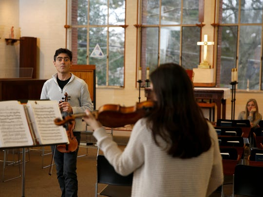 Yuliyan Stoyanov, left, talks with Madelyn Deininger, 15, a freshman at Walnut Hills High School, during a violin lesson, as her mother Carolyn, far right, listens, Thursday, March 24, 2016, at Holy Trinity Episcopal Church in Madeira, Ohio. Stoyanov, a Bulgarian-born violinist and College Conservatory of Music alumnus and current faculty member, faces deportation after two rejected appeals.