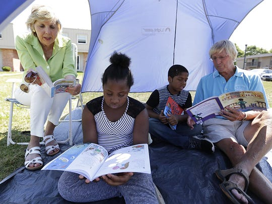 Morning Rotarians Valerie and Wayne Graczyk of Fond du Lac volunteer time to read with Zekria Sanders and Zekhi Hutchinson during Pier Elementary School's Picnic and Pages, held this summer at Maplewood Commons apartment complex.