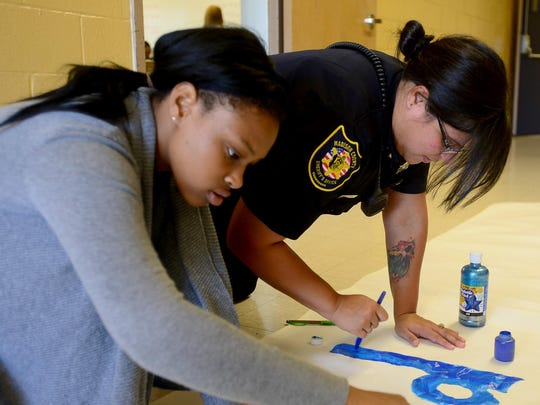 Madison County Sheriff's Deputy and School Resource Officer Rebecca Hutson helps North Side High School cheerleader Alicia Long paint the football banner Thursday.