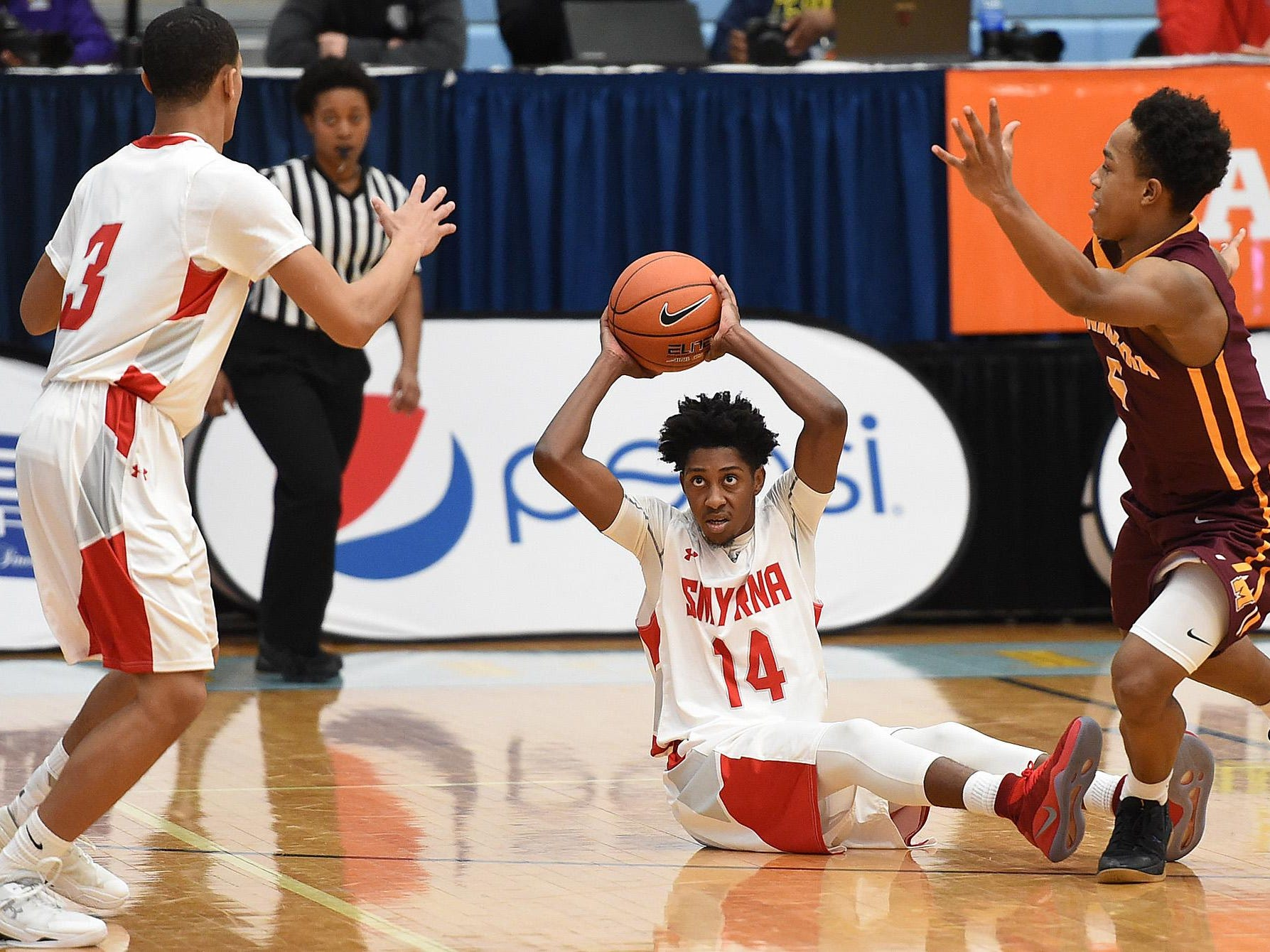 Smyrna's #14 Anthony Watson pass's the ball to #3 Zion Cole as The Annual Slam Dunk to the Beach Basketball Tournament started at Cape Henlopen High School in Lewes on Tuesday December 27th with Smyrna HS (white) hosting Bishop McNamara HS from Forestville, Md.