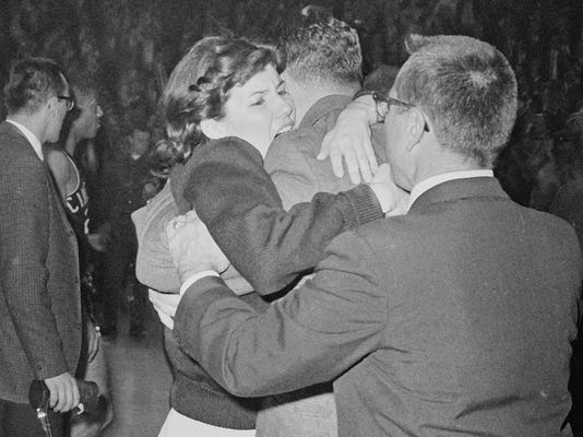 FILE - In this March 23, 1963, file photo, Kathy Ireland gives her father, Loyola coach George Ireland, a hug after they defeated Cincinnati 60-58 in overtime in the National Collegiate basketball finals in Louisville, Ky. The Ramblers play Nevada on Thursday, March 22, 2018, after two thrilling wins to reach the Sweet 16, earning more wins this season than the team that won the 1963 title. (AP Photo/File)