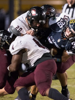 Gulf Breeze High School's Tyler Dittmer, (No. 36) get wrapped up by the Navarre High Shcool defense during the Dolphin's final regular-season home game Friday night.
