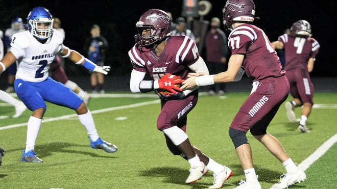Osage junior quarterback Brockton McLaughlin hands the ball off to sophomore Eric Hood in a game against Boonville on Friday, October 2, in Osage Beach. Hood finished the game with 215 rushing yards and a touchdown.