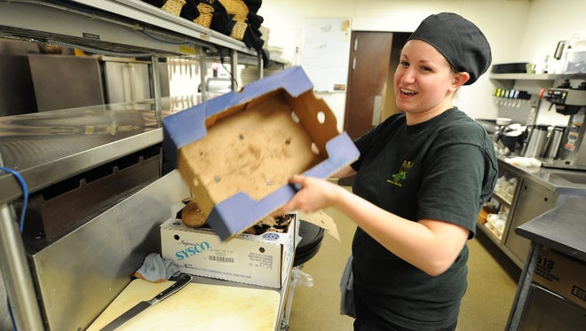 Korina Schroeder, a line chef at Black and Tan Restaurant, does food prep with portobello mushrooms after the initial lunch rush subsided June 30, 2016.