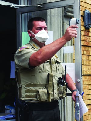 Logan County Sheriff Jason Massey checks the temperature of an individual arriving for a district court appearance last week in Booneville.