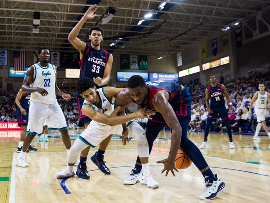 FGCU guard Dinero Mercurius (31) scrambles for the ball during their game against Florida Atlantic University at Alico Arena on Tuesday in the Eagles' 92-88 loss.