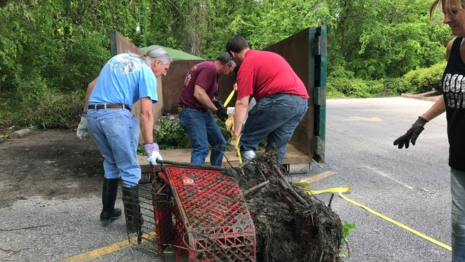 Larry Hart, Mike Barnhill and City Engineer Brent Schmitt help drag the first shopping cart pulled from 'Cart Creek' on Sunday afternoon as Evansville Stormwater Coordinator Karan Barnhill looks on. 'Cart Creek' is a North Side creek littered with more than 60 shopping carts. Dozens of volunteers removed nearly 30 from the creek Sunday.