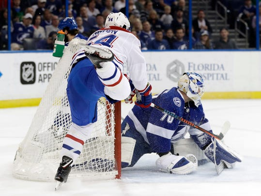 Tampa Bay Lightning goaltender Louis Domingue (70) stops a shot by Montreal Canadiens left wing Charles Hudon (54) during the first period of an NHL hockey game Saturday, March 10, 2018, in Tampa, Fla. (AP Photo/Chris O'Meara)