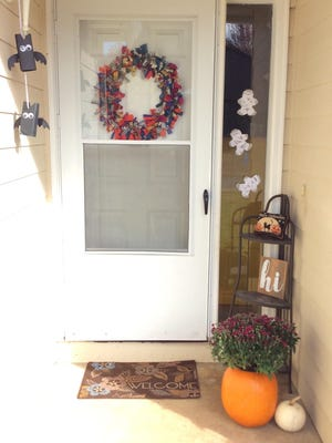 Soapbox bats, a fabric wreath, mummies and a pumpkin planter decorate a porch for Halloween.