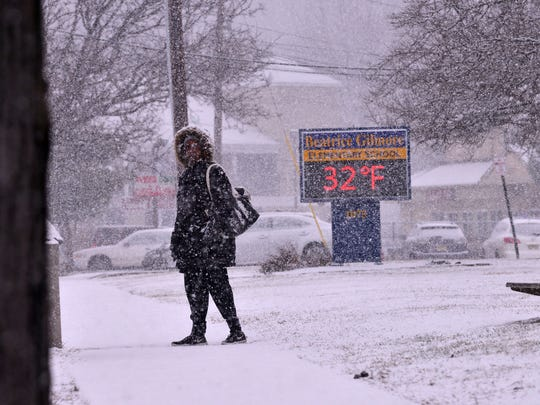 A lady waits for her bus on McBride Ave. during an early day snow fall in Woodland Park, NJ. January 31, 2017.