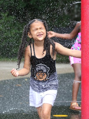 Jocelyn Morales, 6, keeps her eyes closed as she spins through a misting area of the spray park at Humboldt Recreation Center.
